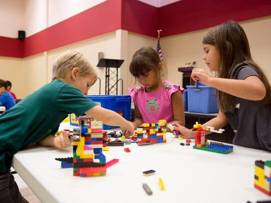 Children play with LEGO bricks.