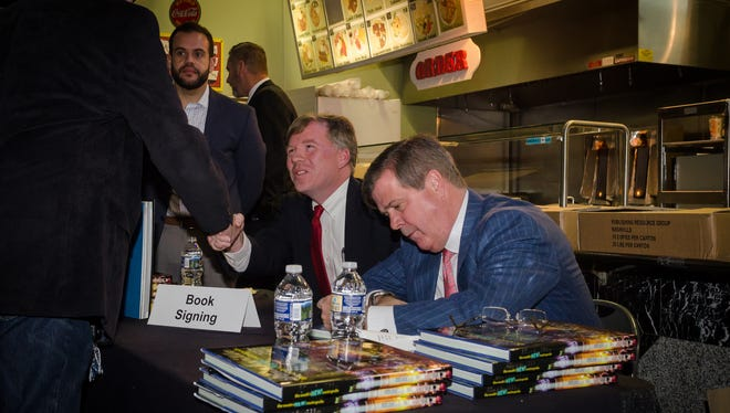 """Michael Cass, left, and former Mayor Karl Dean, authors of """"Nashville: The South's New Metropolis,"""" sign copies of the book during a signing at the Nashville Farmers' Market."""
