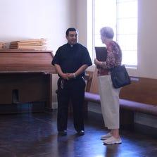 Father Alfredo Valdez, left, speaks with church member Barbara Powell.