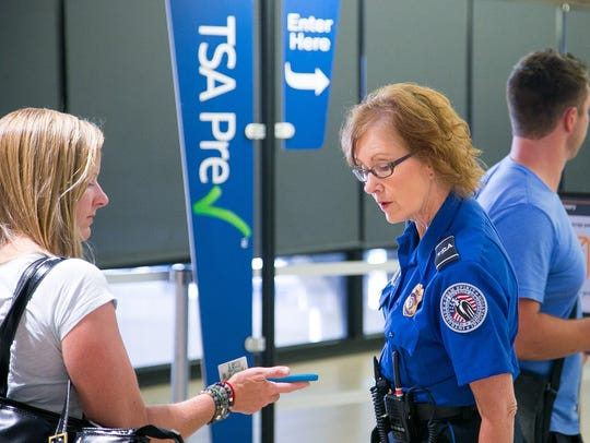 TSA agent Sherri Kural directs passengers to the TSA