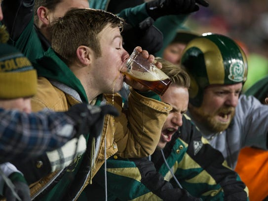 A Colorado State fan drinks a beer while others cheer