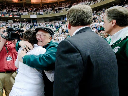 Carl Izzo (second from left) hugs his daugher-in-law Lupe Izzo (from left) as her husband MSU Men's Basketball Head Coach Tom Izzo and Steve Mariucci look on after MSU claimed a share of the Big Ten title by defeating Michigan Sunday March 7, 2010 in East  Lansing.