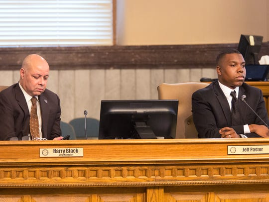 Cincinnati City Manager Harry Black, left, listens