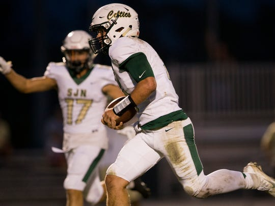 St. John Neumann quarterback Jensen Jones (5) carries the ball towards the end zone as teammate Hunter Jones (17) motions touchdown in the first half of action at Community School of Naples Friday, October 20, 2017 in Naples. CSN would lead at the half 13-12.