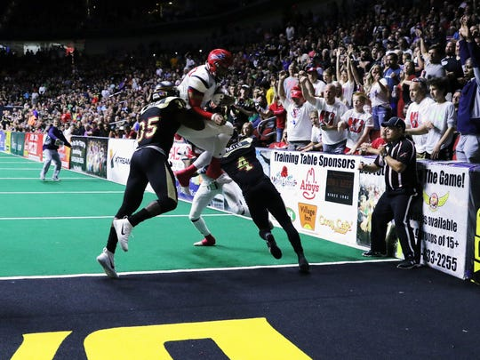 Sioux Falls Storm QB Lorenzo Brown Jr leaps into the endzone for the score during the 2nd half while Coach Kurtess Riggs cheers in the background.