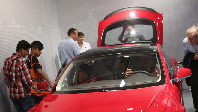 Visitors look at a Tesla Model S electric car at the Panasonic stand at the 2014 IFA home electronics and appliances trade fair on September 5, 2014 in Berlin, Germany.