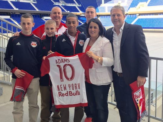 Tyler Adams, front center, poses with his mother Melissa Russo, stepfather Darryl Sullivan (back) and Sullivan's sons, as well as James Grant Sports global director Lyle Yorks, right.