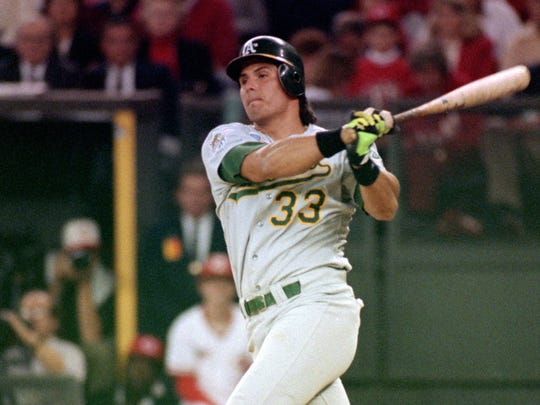 Jose Canseco of the Oakland Athletics watches the flight of the ball during Game 2 of the 1990 World Series against the Cincinnati Reds at Riverfront Stadium on Oct. 17, 1990, in Cincinnati, Ohio.