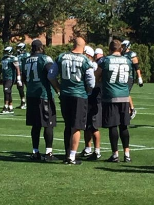 Eagles' offensive linemen Jason Peters (71), Lane Johnson (65) and Allen Barbre watch practice Tuesday.