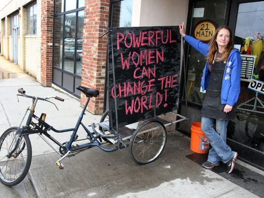 Kerri Martin, founder and executive director of Second Life Bikes, stands outside the front door of her shop next to her billboard bike in Asbury Park, NJ Wednesday April 9, 2015. Martin changes the clever saying on her billboard bike weekly to reflect on an upcoming local event, a holiday or news story. (for the POWERFUL WOMEN: DEFINED, GIRL POWER, PORTRAIT OF A STRONG WOMAN visual series)