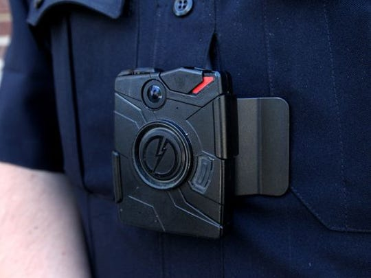 This Sept. 22, 2014 photo shows a black camera clipped to a police uniform in Kent County, Michigan. A local group is asking Springfield City Council to demand body cameras for Springfield police officers.