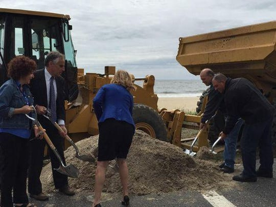 Long Branch officials ceremoniously shovel sand Thursday at a groundbreaking ceremony for the city's boardwalk reconstruction.
