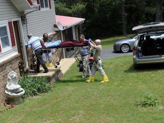 Authorities remove Robert McCorkle's body from his Flippin home on June 6, 2013. Authorities are still searching for McCorkle's killer.