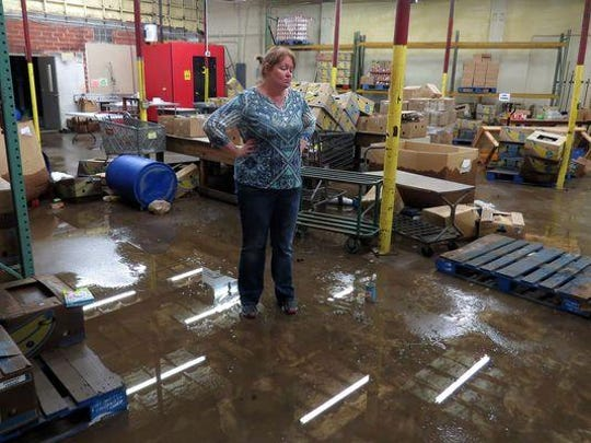DeDe Flounlacker, executive director of Manna Food Pantries, looks over the muddy and wet floor where the organization stored thousands of food items, most of which had to be discarded after flood waters in May 2014 swirled through the building, upending refrigerators and desks and spoiling boxes of food.