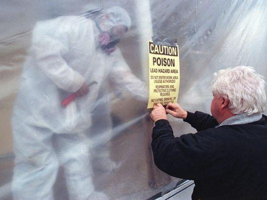 """File photo of a """"lead hazard area"""" sign being posted on an Asbury Park home during the removal of lead paint."""
