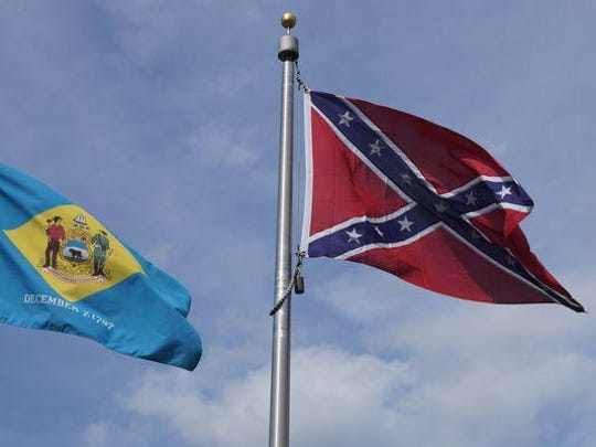 The Confederate flag flies alongside the Delaware state flag over the Delaware Confederate Monument on Wednesday. Officials say there are no plans to remove the flag, which has been taken from several sites across the country following the shooting at a South Carolina church.