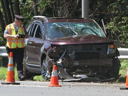 An Ocean Township police officer walks past a vehicle involved in a collison on Rt 18 southbound, south of Deal Road, in the township, Thursday.