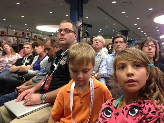 Matt Hill, left, with his children Sam and Sarah as they wait to hear for news on New Horizons approach to Pluto