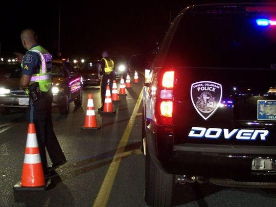 A DUI checkpoint slows vehicles in Dover. These operations are funded partially by diverted highway construction funds.