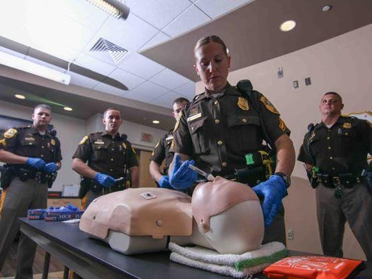 New Castle County Police Officer First Class L. Taylor administers water, which simulates the drug Narcan, into a practice mannequin at the New Castle County Police public safety building. Narcan, a nasal spray, is used to reverse the effects of opiates during an overdose.