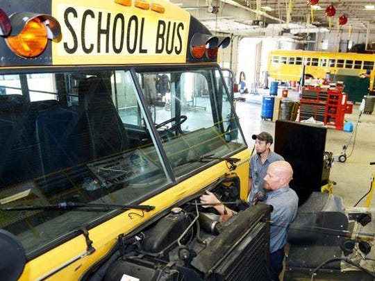 Buncombe County Schools mechanics Brian King and Chance Barry inspect a bus's wiring at the Woodfin bus complex Friday. County schools reopen Wednesday.