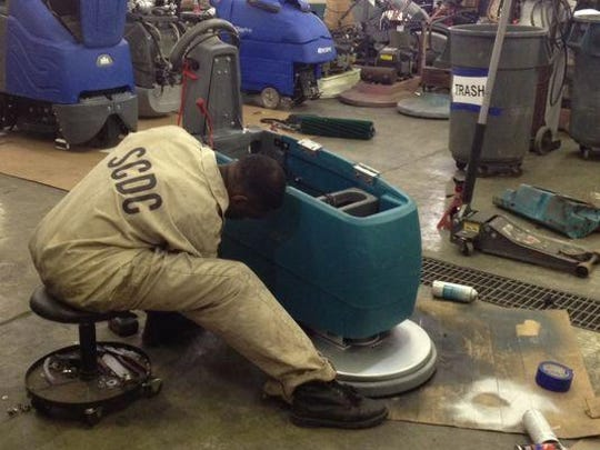 An inmate refurbishes a buffing machine while working for Southeastern Equipment, a service program.