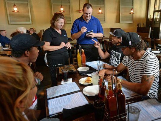 Smoke on the Water waiters Lynn Lupperger, left, and Jon Schweizer take the order of Greenville Drive player Joseph Monge at the restaurant in downtown Greenville. Also pictured are, from left, Dr. Bobbi Siefert, Carlos Pinales, and Edwar Garcia.