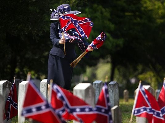 Strong winds send confederate flags flying as Karen Prewitt collects them after the Confederate Memorial Day ceremony at Magnolia Cemetery in Charleston, S.C., on May 10, 2011. (Photo: Grace Beahm, AP)