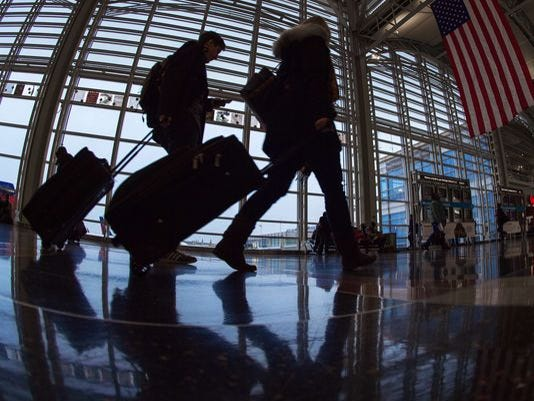 Airline travelers at Ronald Reagan National Airport walk to a Transportation Security Administration (TSA) security checkpoint prior to traveling in this November 2014 file photo.