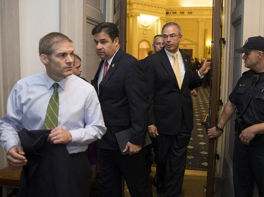 Rep. Jim Jordan, R-Ohio, left, followed by Rep. Raul Labrador, R-Idaho, and other members of the House Freedom Caucus, leave a hearing room on Capitol Hill on Oct. 8.