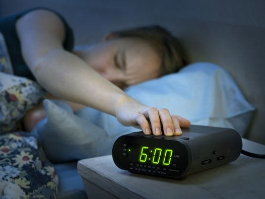Woman waking up with an alarm clock. (Photo: Elenathewise, Getty Images/iStockphoto)