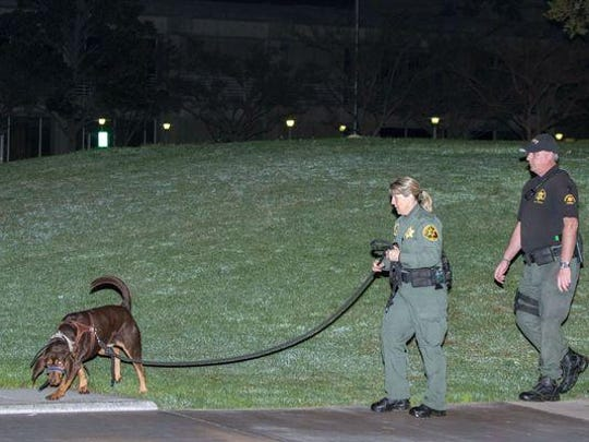Orange County sheriff's deputies and a search dog investigate early Saturday after three jail inmates charged with violent crimes escaped from Central Men's Jail in Santa Ana, Calif.