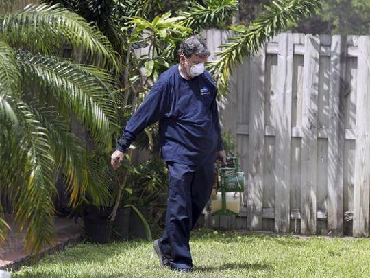 Giraldo Carratala, an inspector with the Miami- Dade County mosquito control unit, sprays pesticide in the yard of a home in Miami, Fla. The department was responding to complaints about mosquitoes by a resident in the neighborhood. Health officials are concerned about the spread of the Zika virus in the U.S., and they still need more money to fight the mosquitoes that spread it.