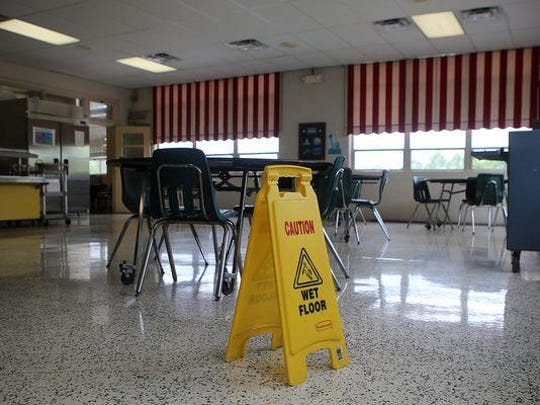 A wet floor sign is seen Tuesday in the cafeteria at Parkview Learning Center. The cafeteria was one of the rooms that flooded, causing the school to be shut down for the day.