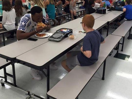 FSU receiver Travis Rudolph bites into a slice of pizza as he joins Bo Paske for lunch Tuesday at Montford Middle School.