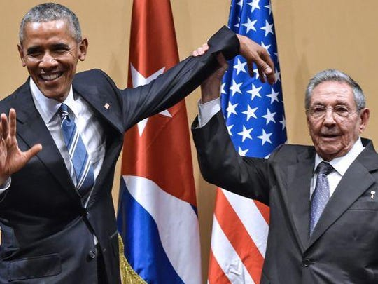 Cuban President Raul Castro raises President Obama's hand during a meeting at the Revolution Palace in Havana on March 21.