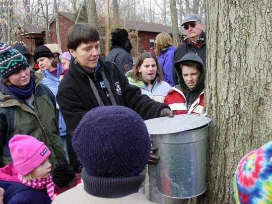 Visitors to the Outdoor Education Center in Chatham Township watch a maple sugaring demonstration during last year's festival.