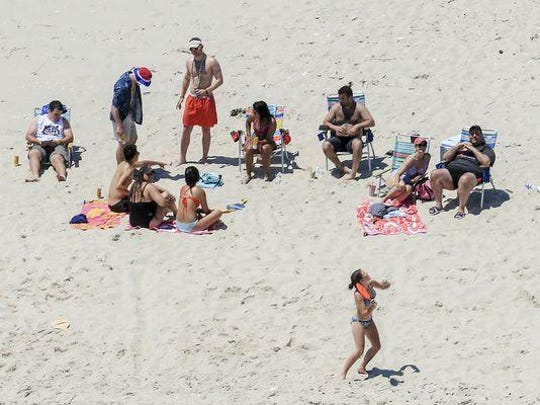In this Sunday photo, Gov. Chris Christie, right, uses the beach with his family and friends at the governor's summer house at Island Beach State Park.