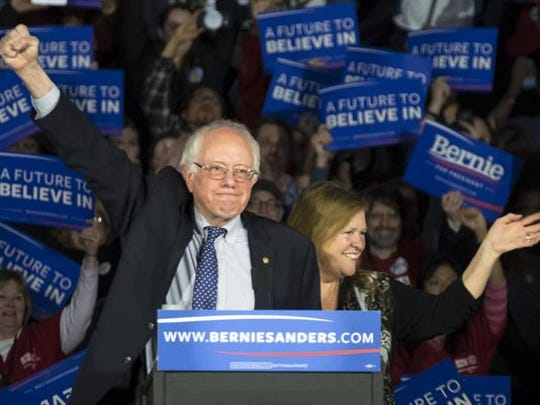 Democratic presidential candidate Sen. Bernie Sanders, I-Vt., and his wife, Jane, acknowledge the crowd as he arrives for his caucus night rally in Des Moines on Monday, Feb. 1, 2016.