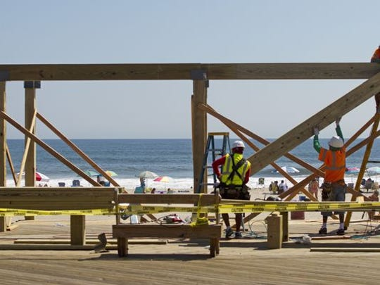 New Jersey employers expect better sales and profits next year, but they don't sound ready to hire in waves, a survey by a state business lobby group released Thursday found. Workers construct gazebos along the boardwalk in Seaside Heights in this August file photo.