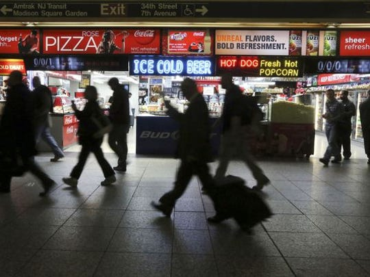 This 2013 photo shows evening rush hour commuters making their way past the food concessions inside New York's Penn Station.