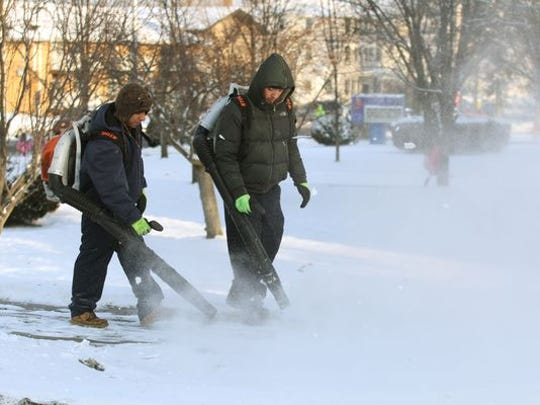 Lakewood, NJ, Board of Education employees Misael Tejada (right) and Eduardo Villasenor, both from Lakewood, use leaf blowers to clear the snow off walkways around the Clifton Avenue school after a February 2014 snow storm.