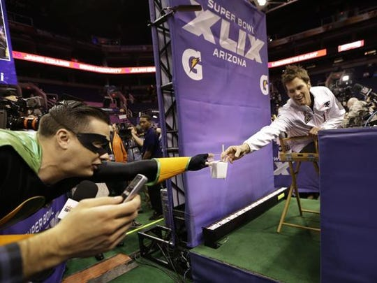 A reporter from Nickelodeon gives New England Patriots' Tom Brady noodles with chop sicks during media day for NFL Super Bowl XLIX football game Tuesday, in Phoenix.
