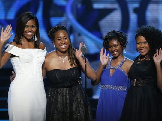 First Lady Michelle Obama, left, waves while standing on stage with Making A Difference award winners, from left, Kaya Thomas, Chental-Song Bembry and Gabrielle Jordan during a taping of the Black Girls Rock award ceremony at the New Jersey Performing Arts Center, Saturday, March 28, 2015, in Newark.