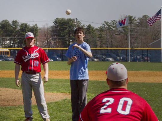 Wall High School student James MacInnes, who has Autism, threw out the first pitch to Wall catcher Dan Wondrack Saturday before the Wall-Old Bridge game.