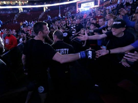 Spectators cheer as Luke Rockhold leaves the octagon after defeating Lyoto Machida in a UFC mixed martial arts bout, Saturday, in Newark, N.J.