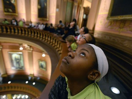 Students from Burton Glen Academy in Burton, Mich., look at the huge paintings above them in the Rotunda of the Capitol during a tour of the building in Lansing on April 20, 2015.