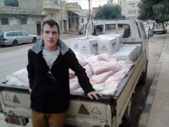 In this undated photo provided by the Kassig Family, Abdul-Rahman Peter Kassig is shown with a truck loaded with supplies. The Islamic State group released a graphic video Nov. 16 in which a black-clad militant claimed to have beheaded him.