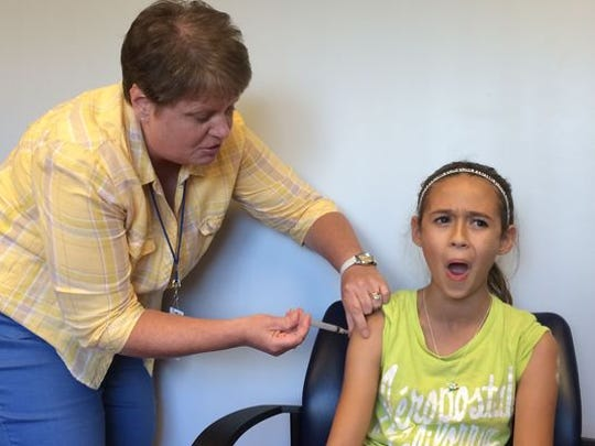 FILE - Nancy Cohen, public health nurse with the Manitowoc County Health Department, gives 11-year-old Josie Decker of Manitowoc one of three immunizations in this September 2014 file photo.