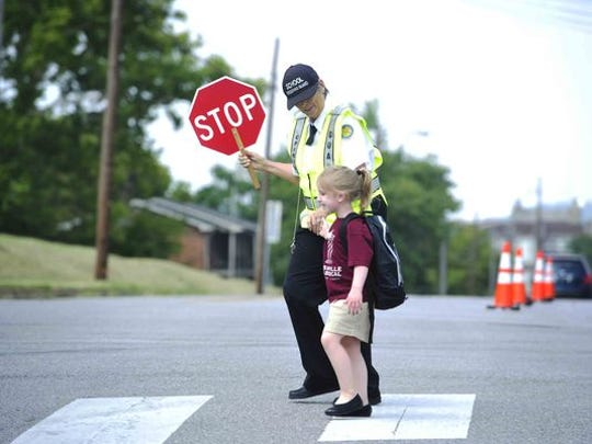 Crossing guard Sue Clark walks Olivia Bogard, 5, across South 10th Street in front of Nashville Classical Charter School.